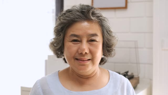 カメラを見て、自宅でリビングルームで笑っているシニア女性。ホームコンセプトで幸せな老化 - 中国人点の映像素材/bロール