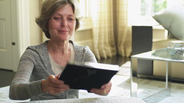 ms senior woman looking at family photos / tenafly, new jersey, usa - tischflächen aufnahme stock-videos und b-roll-filmmaterial