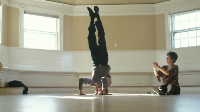 WS, Senior woman looking at man doing headstand in empty room, Hingham, Massachusetts, USA