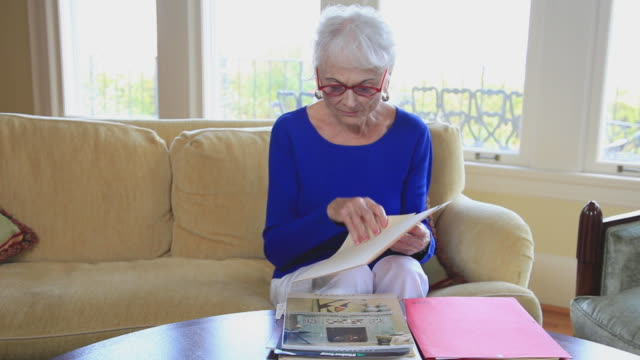 ms senior woman looking at paperwork in her living room / portland, oregon, usa - portland oregon homes stock videos & royalty-free footage