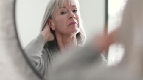 senior woman looking at reflection in mirror - bathroom stock videos & royalty-free footage
