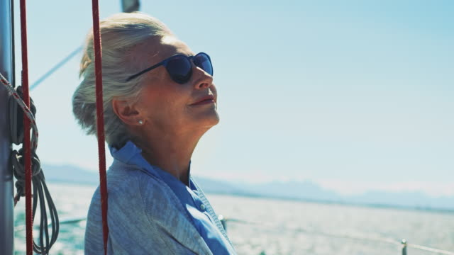 senior woman looking away in yacht - senior women stock videos & royalty-free footage