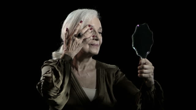 senior woman looking in mirror and adjusting appearance - eleganz stock-videos und b-roll-filmmaterial