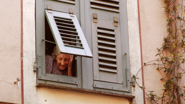 Senior woman looking out a window to street, Ajaccio, Corsica