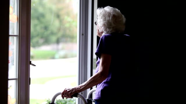senior woman looking out front door - walking frame stock videos & royalty-free footage