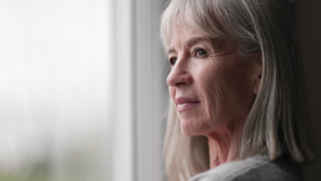 Senior woman looking out of window thinking