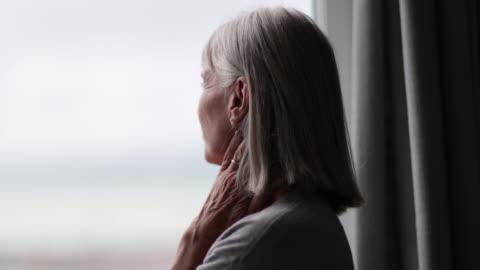 stockvideo's en b-roll-footage met senior woman looking out of window thinking - solitair