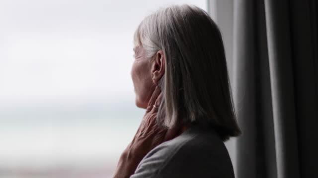 senior woman looking out of window thinking - isolamento video stock e b–roll
