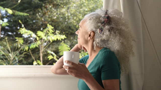 senior woman looking out window and sipping drink - curly stock videos & royalty-free footage