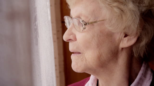 senior woman looking out window - senior women stock videos and b-roll footage