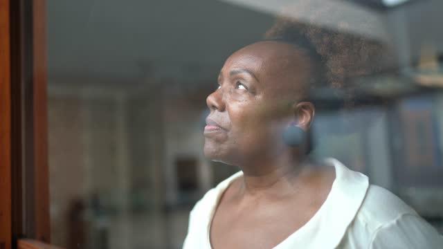 senior woman looking through the window - looking through window stock videos & royalty-free footage