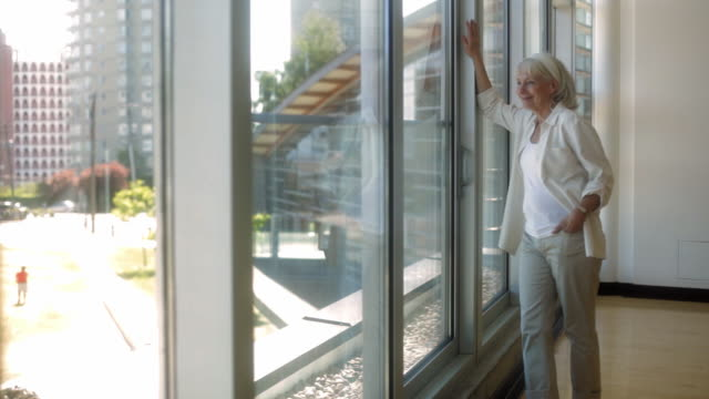 ms pan senior woman looking through window, standing in corridor / vancouver, british columbia, canada - only senior women stock videos & royalty-free footage