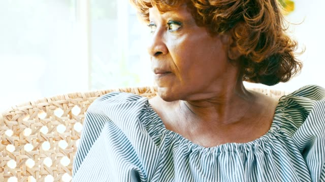 senior woman looks through window in her home - wicker stock videos & royalty-free footage