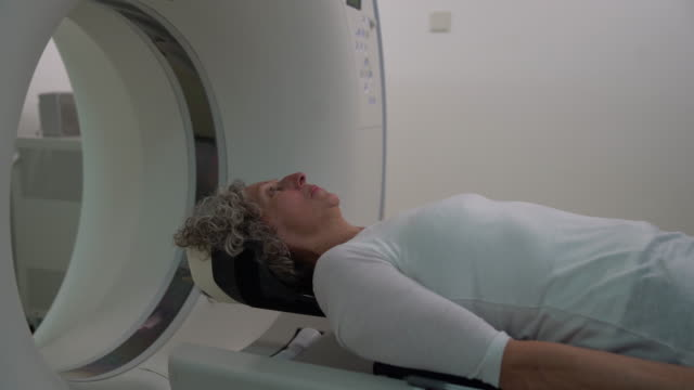 senior woman lying down on a flat bed scanner ready for a mri brain scan - diagnostic medical tool stock videos & royalty-free footage