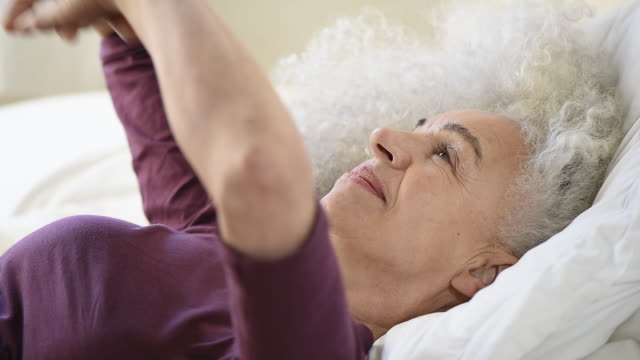 senior woman lying in bed stretching
