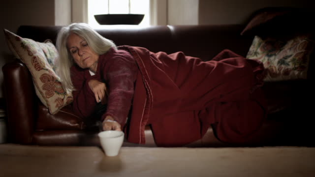 MS Senior woman lying on couch reaching for hot drink and drinking / Kingston, New York, USA