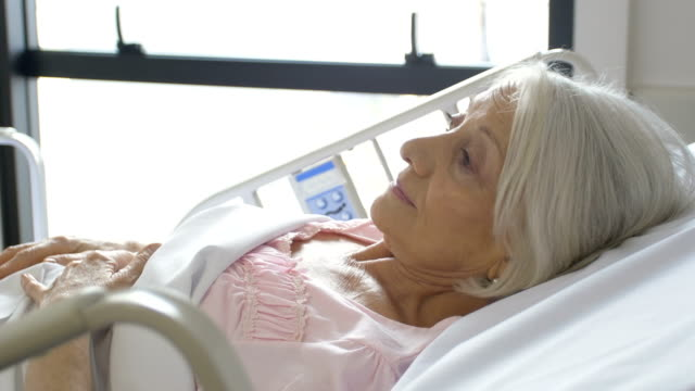 senior woman lying on hospital bed - telecamera traballante video stock e b–roll