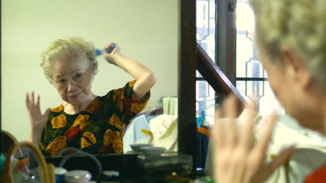 senior woman makes a hairstyle at home - brushing hair stock videos & royalty-free footage