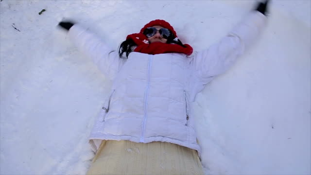 Senior woman makes a snow angel