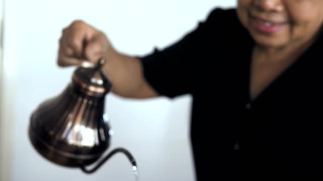 senior woman makes coffee - 60 69 anni video stock e b–roll