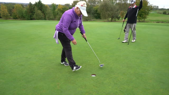 a senior woman making a short putt in the hole. - sun visor stock videos and b-roll footage