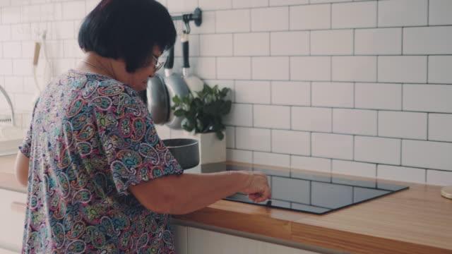 自宅で朝に卵を沸かす先輩女性。 - 沸騰する点の映像素材/bロール