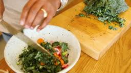 Senior woman making leaf vegetable salad at home