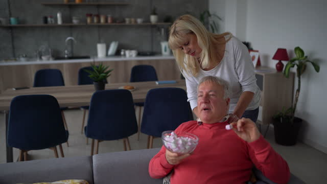 senior woman massaging her husband while he's relaxing at home - body care stock videos & royalty-free footage
