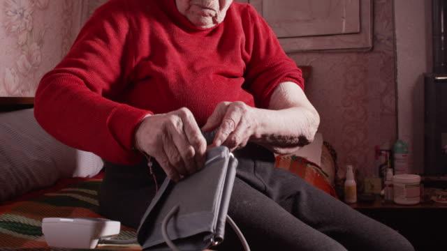 senior woman measuring blood pressure at home. - blood pressure gauge stock videos & royalty-free footage