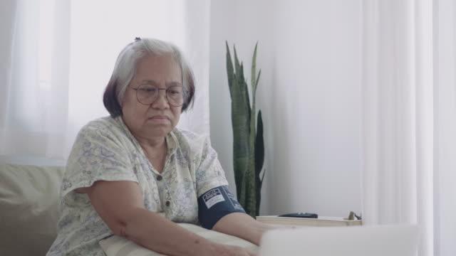 senior woman measuring blood pressure with laptop - senior women stock videos & royalty-free footage