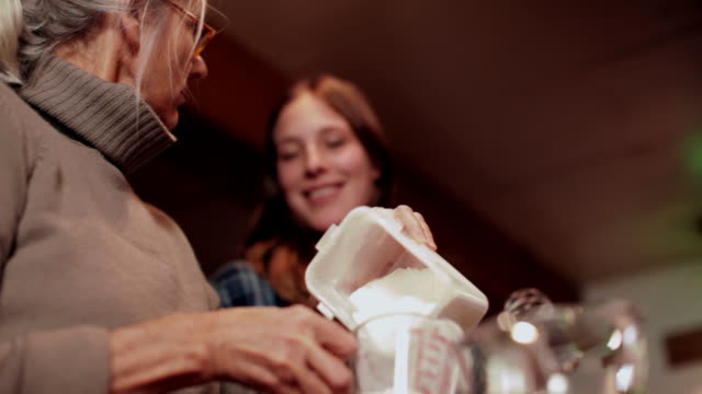 MS TD Senior woman measuring flour and putting in large bowl and showing to daughter / Kingston, New York, USA