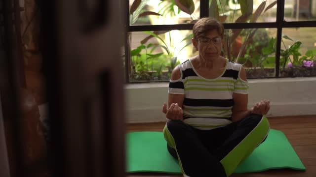vidéos et rushes de femme âgée méditant à la maison - assis en tailleur