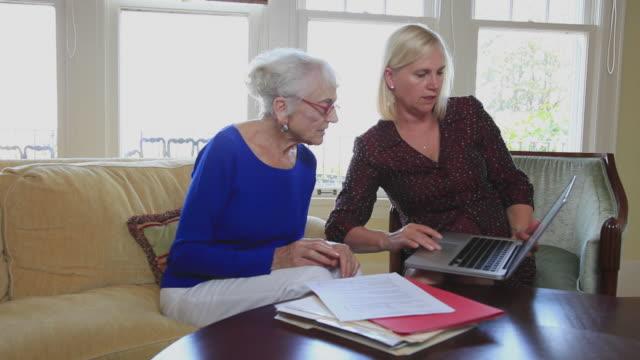 ms senior woman meeting with financial adviser at home / portland, oregon, usa - portland oregon homes stock videos & royalty-free footage