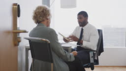 Senior Woman Meeting With Male Financial Advisor In Office