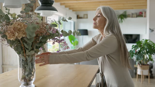 senior woman moving dried flower arrangement in apartment - vase stock videos & royalty-free footage