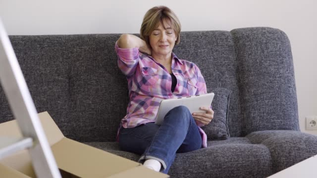 senior woman moving into a new apartment - neckache stock videos & royalty-free footage