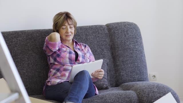 vídeos de stock e filmes b-roll de senior woman moving into a new apartment - dor no pescoço