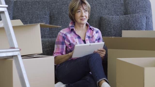 新しいアパートに移動しているシニア女性 - 床に座る点の映像素材/bロール