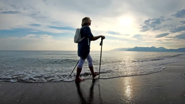 senior woman nordic walking on the beach - hiking pole stock videos & royalty-free footage