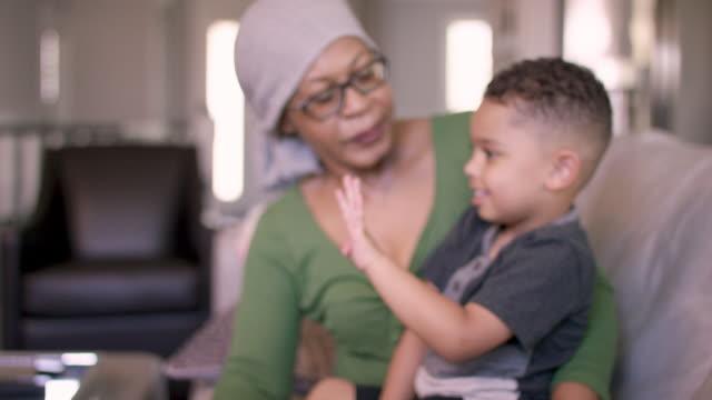 vídeos de stock, filmes e b-roll de uma mulher sênior da descida africana com cancro está em casa que prende seu neto. ela parece estar contente e em paz. - radioterapia