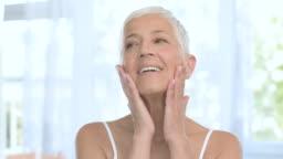 Senior woman oman touching her skin.