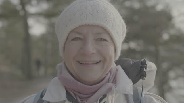 フラット カラー プロファイルのカメラに探してハイキングに年配の女性 - グレースケール点の映像素材/bロール
