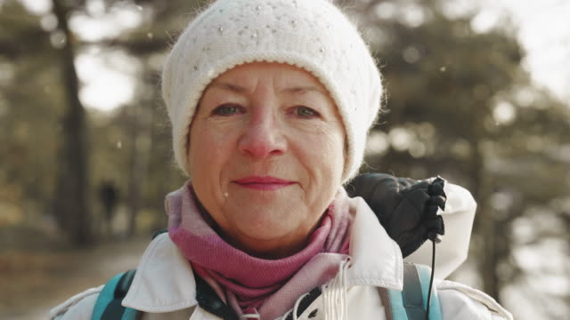 senior woman on a hike looking into camera - winter stock videos & royalty-free footage