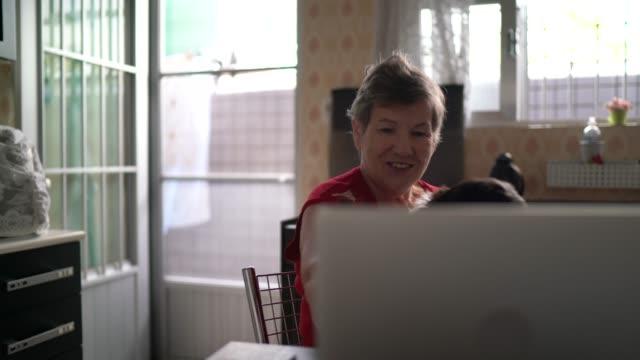 Femme aîné sur une affaire de vidéo utilisant l'ordinateur portatif à la maison