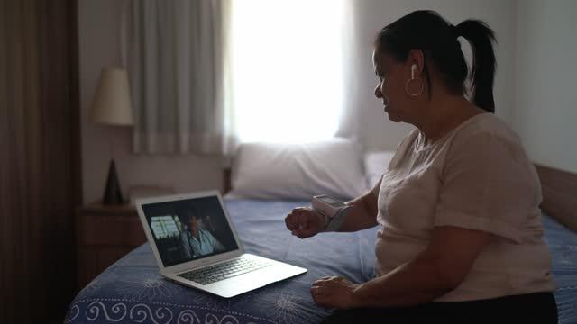 vídeos y material grabado en eventos de stock de mujer mayor en una videomeda de telemedicina con un médico en casa - visita a domicilio