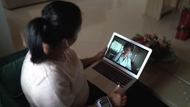 donna anziana in una videochiamata di telemedicina con un medico a casa - misurare il polso video stock e b–roll
