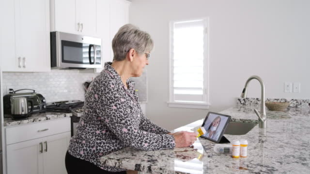 senior woman on a virtual doctor visit - visit stock videos & royalty-free footage