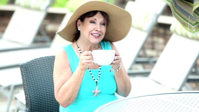 ältere frau am pool-deck kaffee trinken - dreiviertelansicht stock-videos und b-roll-filmmaterial