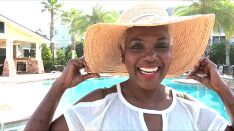 senior woman on vacation by pool with wide brim hat - hat stock videos & royalty-free footage