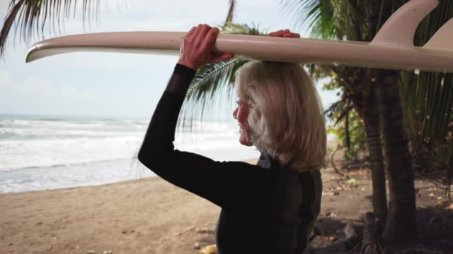 senior woman on vacation holding surfboard turning to laugh at camera excitedly - old diving suit stock videos and b-roll footage
